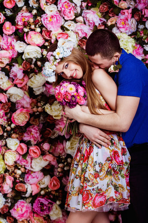 tenderly: A young man is tenderly hugging a beautiful girl near a spring floral wall.