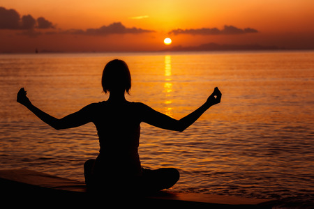 beach scene: A girl is meditating at the sea shore at orange sunset background. Stock Photo