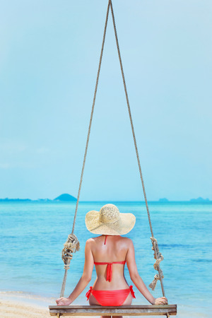 A beautiful girl is swinging at the sea background on a holiday. photo