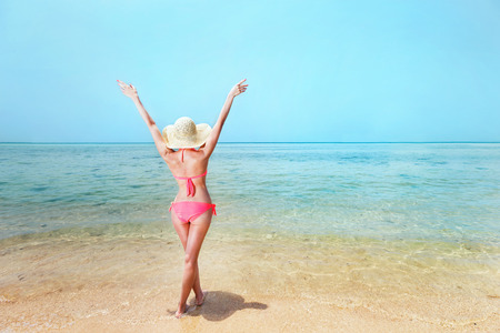 A woman in hat and bikini is raising hands at sunny sea shore background. photo