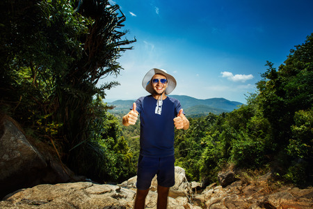 A successful positive man is smiling at the mountain top showing thumbs up gesture. photo