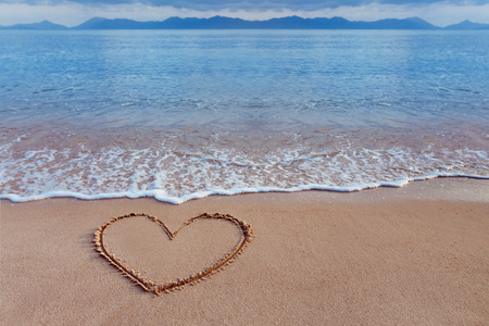 A drawing of a heart as a love symbol on a yellow sand at a seascape background.