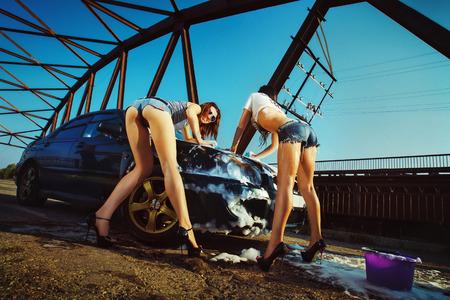 Два желательные девушки в шортах мытья автомобиля на фоне моста и пены вокруг. Концепция частной стиральной службы.