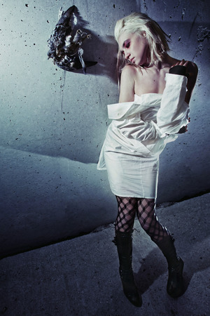 straight jacket: A bizarre insane girl in a straight jacket is standing at a textured wall with a dead pigeon hanging on it.