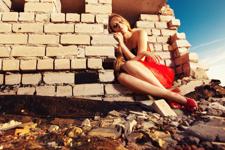 desolate: A beauliful desolate girl in a red dress is sitting at a roof of a building at sunrise background. Concept of life problems. Stock Photo