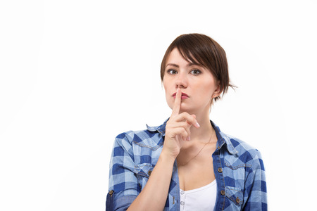 Beautiful woman putting finger to her mouth isolated on white background. Concept of secret, mystery, silence. photo