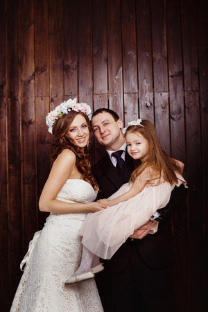 Beautiful pregnant woman in wedding dress and her husband are holding pretty cheerful daughter in arms at a plank wall background. Concept of happy family. photo