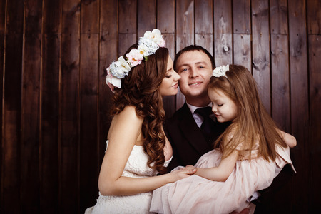 Beautiful pregnant woman in wedding dress is kissing her husband and he is holding pretty  daughter in arms at a wall background. Concept of happy family. photo