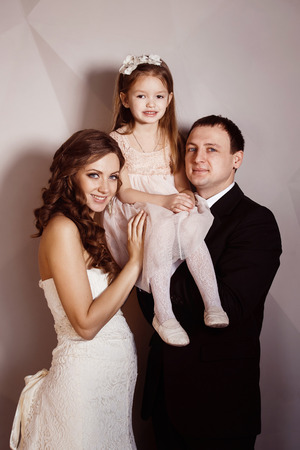 Beautiful pregnant woman in wedding dress and her husband are holding pretty cheerful daughter in arms at a wall background. Concept of happy family. photo