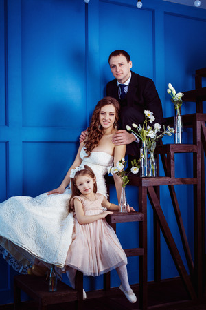 tenderly: Cute little girl and cheerful father who is tenderly holding his beautiful pregnant wife in wedding dress are sitting on a ladder a blue wall background.