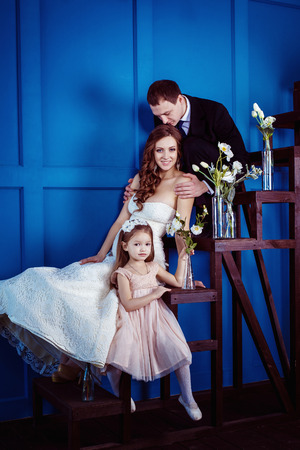 tenderly: A happy family concept. Cute little girl and cheerful father who is tenderly holdiing his beautiful pregnant wife in wedding dress are sitting on a ladder a blue wall background.
