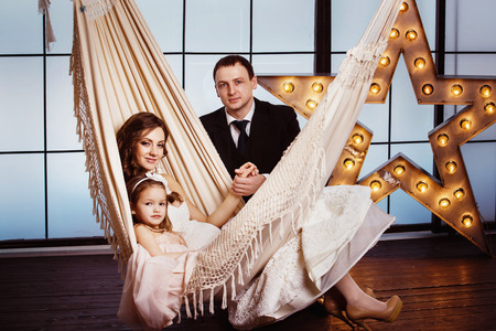 A happy family concept. Beautiful pregnant wife in wedding dress and her cute daughter are sitting in a hammock at a star background while young father is holding her by hand. photo