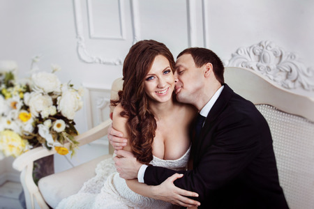 A beautiful wedding pair is kissing and tenderly holding by hands sitting on sofa at home background.