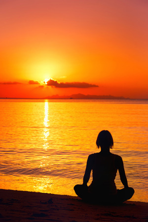 A silhouette  of meditating woman at the sea shore at orange sunset background. photo