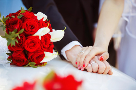 Picture of man and woman hands with wedding ring holding tenderly and a red flowers bouquet.