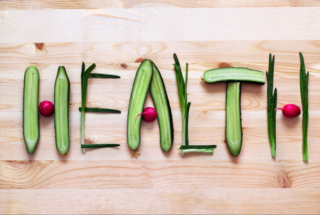 Healthy eating. Word Health made of vegetables isolated on carving board. Standard-Bild