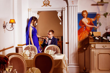 tenderly: Elegant man is tenderly  kissing his beautiful girl hand standing on a knee in arch of a luxury restaurant. Concept of love and rich life.