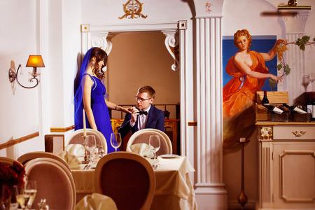 tenderly: Uomo elegante sta teneramente baciando la sua bella in piedi ragazza mano su un ginocchio in arco di un ristorante di lusso. Concetto di amore e di vita ricca. Archivio Fotografico