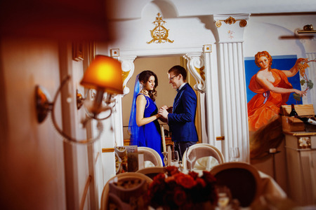 tenderly: Beautiful glamour couple is holding tenderly hands in arch of a luxury restaurant. Concept of love and rich life.