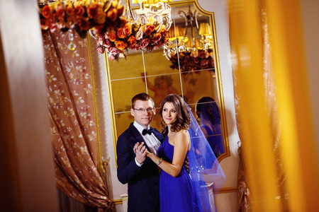 rich life: Beautiful glamour couple is standing and embracing in arch of a luxury restaurant. Concept of love and rich life. Stock Photo