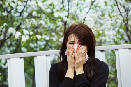 sniffer: Closeup portrait of a young woman sneezing in a sniffer at spring flowers blossoms background that causes allergy.