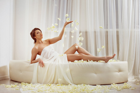 romance bed: Attractive slim woman in white cloth with healthy skin is liying on the bed and thowing up flowers pestals.
