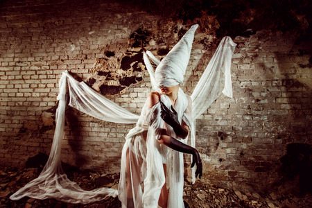 white bandage: Insane evil creature in white bandage is creeping at the dark bricks wall background.
