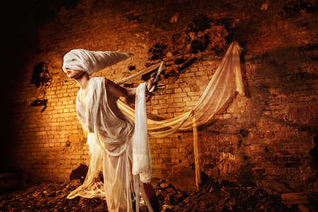 white bandage: Insane evil creature in white bandage is tied to the dark bricks yellow wall background and stretching. Stock Photo