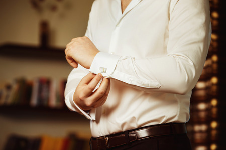 fastens: Close-up image of a man in white shirt who fastens a stud. Concept of a young man morning.