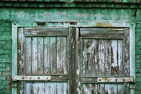 scaled: A wooden vintage scaled door at green bricks wall background.
