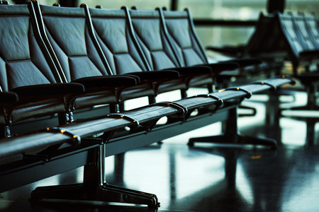 airport terminal: Row of leather chairs in international airport terminal at window background. Stock Photo