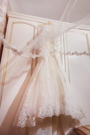 A white long wedding dress is hanging at wardrobe door. Concept of bridal morning. Stock Photo