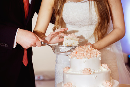 Closeup image of wedding couple cutting beautiful holiday cake with roses. Standard-Bild