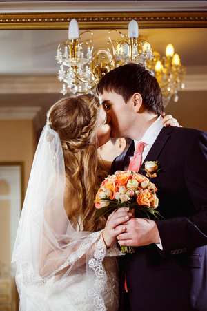 Beautiful loving wedding couple is holding flowers bouquet and kissing at luxury restaraunt interior background. photo