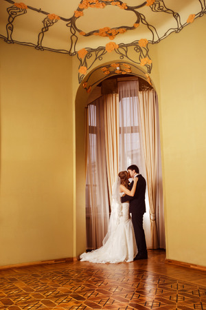 happy family concept: Beautiful elegant wedding couple is kissing in arch at curtained window vintage background. Love and happy family concept.