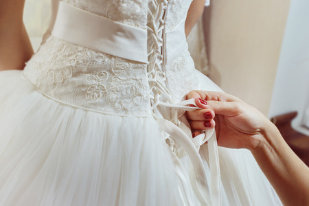 A closeup image of wedding preparations. Bridesmaid is hepling put bride elegant luxury dress. Standard-Bild