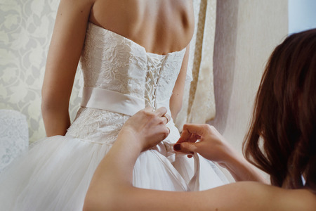 A closeup image of wedding preparations. Bridesmaid is hepling put bride elegant luxury dress. Stock fotó