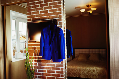 garderobe: A blue elegant suit is hanging on a mirror in a modern room with a reflection of a bed at background.