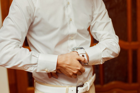 fastens: Close-up image of a man in white shirt who fastens a clock. Concept of a young man morning.