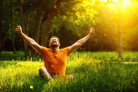 А счастливый человек расслабляется на зеленой траве с прищуром глаз и поднял в небо оружия в солнечный летний день в парке фоне. Концепция благополучия и здорового образа жизни