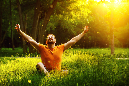 A happy man is relaxing on green grass with squint eyes and raised up to sky arms at sunny summer day at park background. Concept of wellbeing and healthy lifestyle