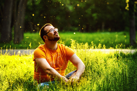 breath: A happy thoughtful dreamer man is sitting on green grass in a park at sunny summer day and looking into future. Concept of relaxation, wellbeing, lifestyle.