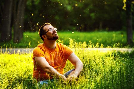 relajado: Un feliz hombre reflexivo so�ador est� sentado en la hierba verde en un parque en el d�a soleado de verano y mirando hacia el futuro. Concepto de relajaci�n, bienestar, estilo de vida. Foto de archivo