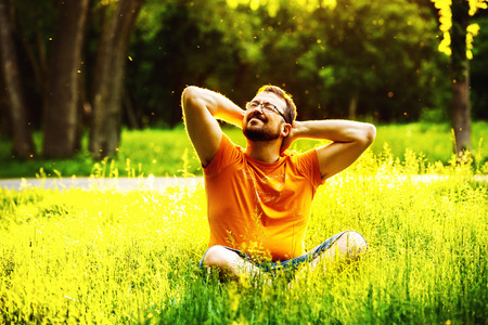 A happy smiling pleased man is sitting on green grass and folding arms behind head at sunny summer day at park background. Concept of wellbeing and healthy lifestyle Standard-Bild