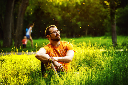 A serious thoughtful man is sitting on green grass in a park at sunny summer day at trees background. Concept of wellbeing, lifestyle.