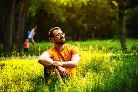 Một người đàn ông chu đáo nghiêm trọng đang ngồi trên thảm cỏ xanh trong một công viên ở ngày mùa hè đầy nắng ở cây nền. Khái niệm an khang, lối sống.