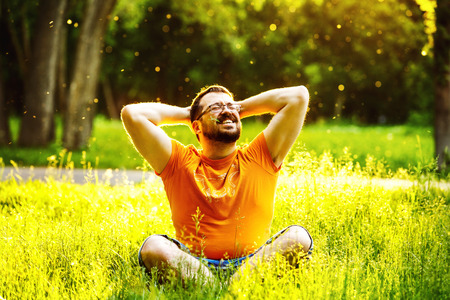 folding arms: A happy smiling carefree man is sitting on green grass and folding arms behind head at sunny summer day at park background. Concept of wellbeing and healthy lifestyle Stock Photo