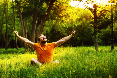 A happy man is sitting on green grass and raising arms up to sky at sunny summer day at park background. Concept of wellbeing and healthy lifestyle