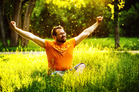 squint: A happy man is relaxing on green grass with squint eyes and raised up to sky arms at sunny summer day at park background. Concept of wellbeing and healthy lifestyle
