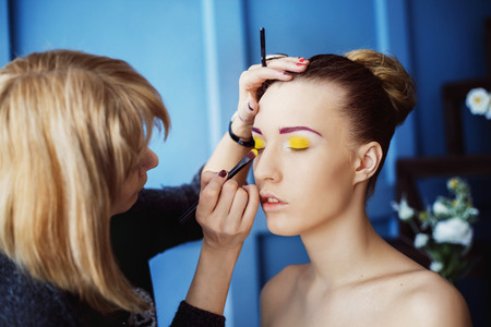 Professional makeup process. Artist is making face style of a young beautiful model at  blue studio background. photo